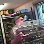 SMH: Man snatches a dispenser of lottery scratch-off tickets.